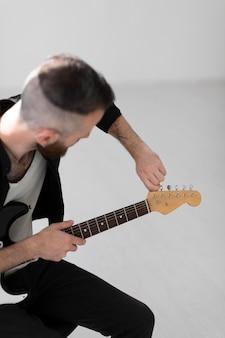 Вид сбоку мужского музыканта, играющего на электрогитаре