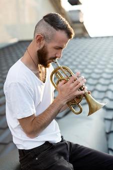 屋根の上でコルネットを演奏する男性ミュージシャンの側面図