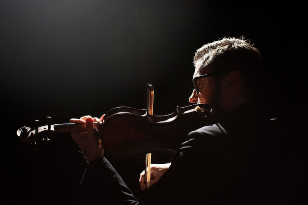 バイオリンを弾く男性ミュージシャンの側面図