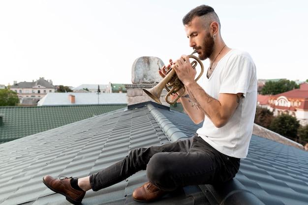 屋根の上にコルネットを持つ男性ミュージシャンの側面図
