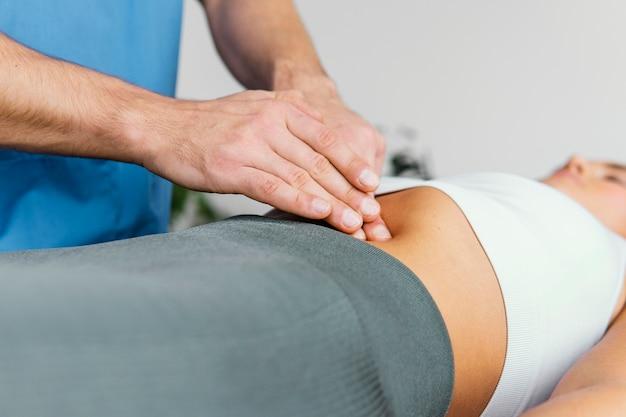 여성 환자의 복부를 검사하는 남성 정골 치료사의 측면보기