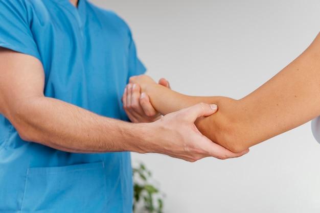 여성 환자의 팔꿈치 관절 움직임을 확인하는 남성 정골 치료사의 측면보기