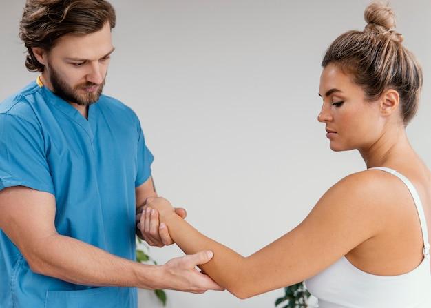 Вид сбоку мужского остеопатического терапевта, проверяющего движение локтя пациентки