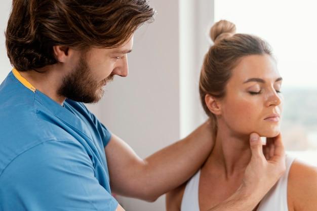 여성 환자의 목 근육을 검사하는 남성 정골 치료사의 측면보기