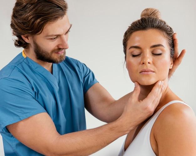 여성 환자의 목을 검사하는 남성 정골 치료사의 측면보기