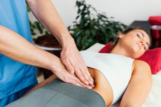 여성의 복부를 검사하는 남성 정골 치료사의 측면보기