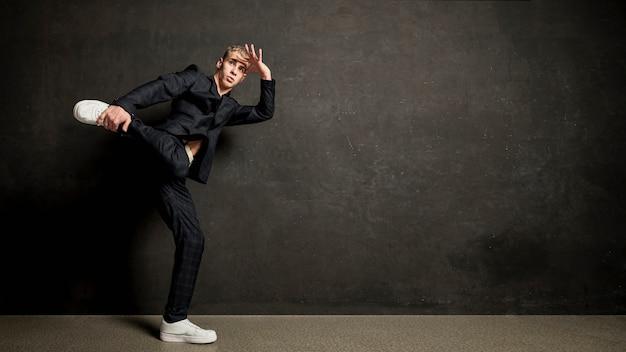 Вид сбоку мужской исполнитель в костюме позирует с копией пространства