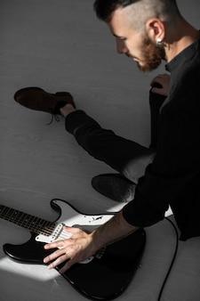 Вид сбоку мужчины-исполнителя, играющего на электрогитаре