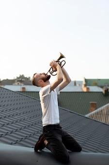 屋上でコルネットを演奏する男性パフォーマーの側面図