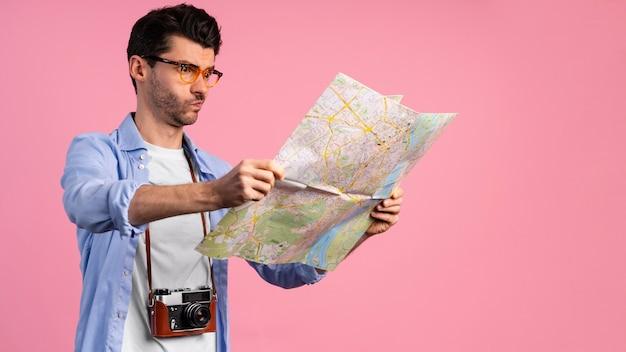 Мужчина-фотограф с помощью карты, вид сбоку