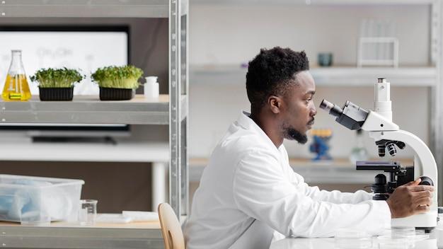 Вид сбоку на мужчину-исследователя в лаборатории, смотрящего через микроскоп