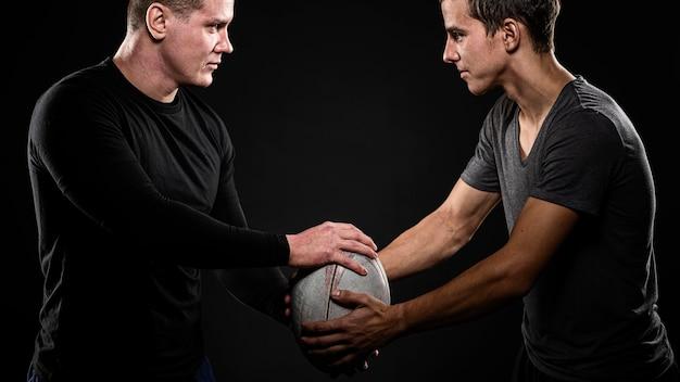 Вид сбоку игроков мужского пола в регби, держащих мяч