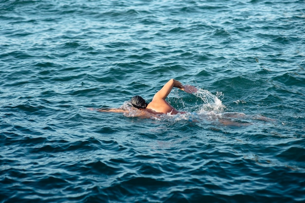 水で泳ぐ男性スイマーの側面図
