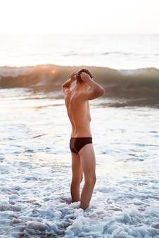 水中でゴーグルとキャップを身に着けている男性スイマーの側面図