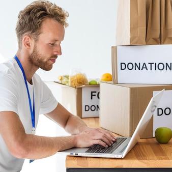 Вид сбоку мужского добровольца, использующего ноутбук