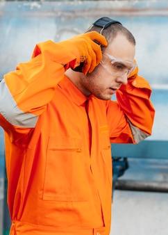保護メガネとヘッドフォンで制服を着た男性労働者の側面図