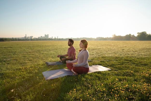 Вид сбоку мужчины и женщины, медитирующие на открытом воздухе на ковриках для йоги