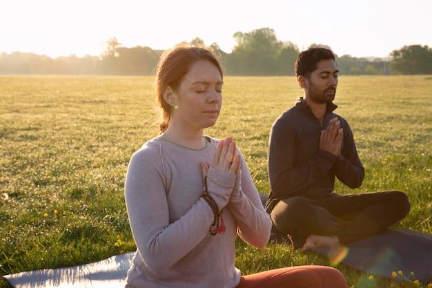 Мужчина и женщина, медитирующие на открытом воздухе, вид сбоку