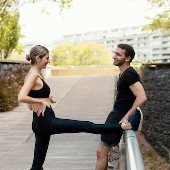 야외에서 운동하기 전에 스트레칭 남자와 여자의 측면보기