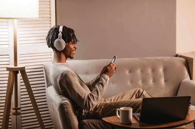Вид сбоку человека дома на диване, используя смартфон и наушники