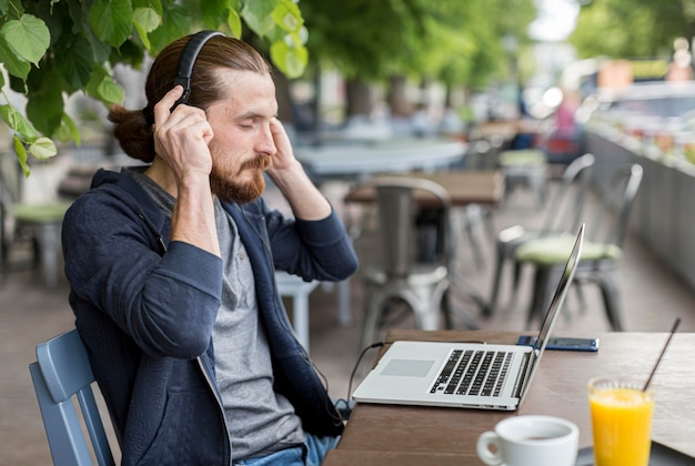 Вид сбоку человека на террасе с наушниками и ноутбуком