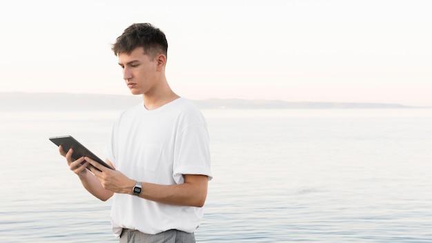 Вид сбоку человека на пляже, держащего планшет с копией пространства