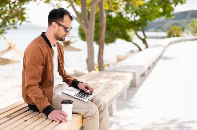 Вид сбоку человека на пляже, работает на ноутбуке