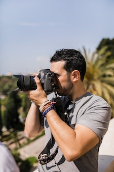 Side view of man capturing pica on camera