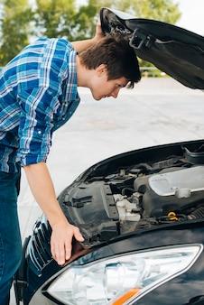 車のエンジンをチェックする男の側面図