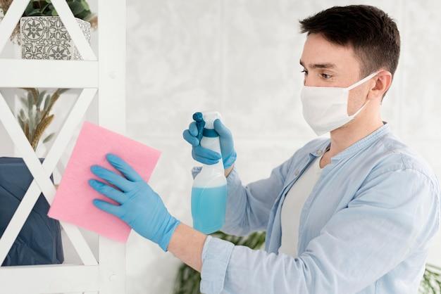 フェイスマスクを着用しながら掃除をする男性の側面図