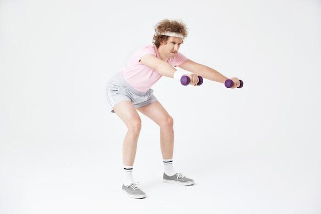 スクワット、筋肉の構築、ハードトレーニングをしている男の側面図