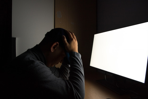 남자 해커의 측면보기 컴퓨터 모니터에 앉아. 어두운 방에서.