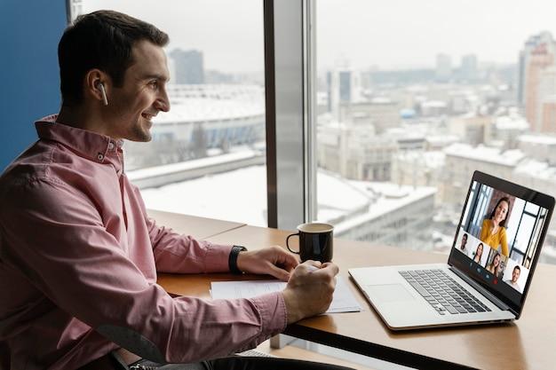 同僚とオンラインビデオ通話をしている男性の側面図