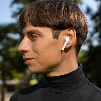 アスレチックウェアと屋外のイヤフォンの男の側面図
