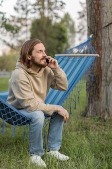 Вид сбоку человека в гамаке, говорить на смартфоне