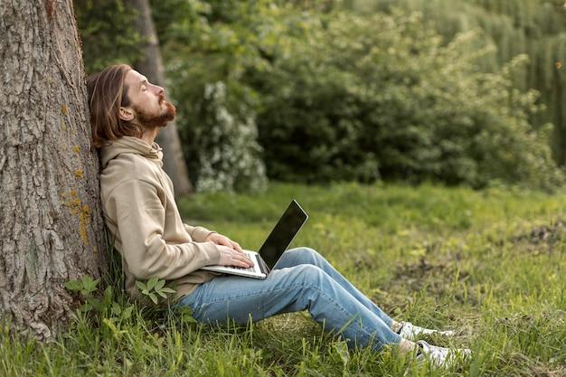 ノートパソコンで自然の中で男の側面図