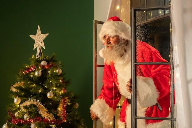 Вид сбоку на человека в костюме санта-клауса, попадающего в дом через окно