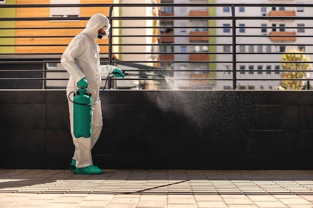 코로나 바이러스 형태의 확산을 방지하기 위해 소독제로 분무기를 들고 야외에서 살포하는 고무 장갑을 착용 한 멸균 보호 유니폼을 입은 남자의 측면보기.