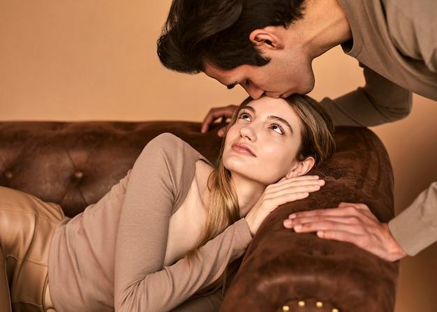 Мужчина целует женщину в лоб, вид сбоку, когда она сидит на диване