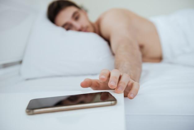 Вид сбоку человека, лежащего на кровати. сосредоточьтесь на телефоне, который лежит возле кровати