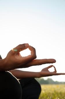 Вид сбоку человека, медитирующего на открытом воздухе с копией пространства