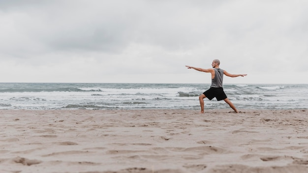 Вид сбоку человека на пляже, занимающегося йогой с копией пространства