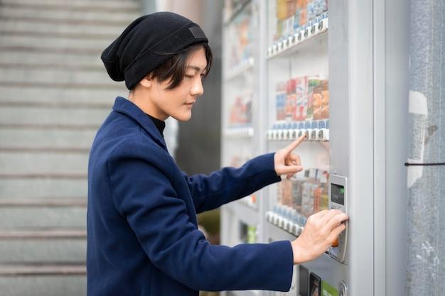 自動販売機から注文する男性の側面図