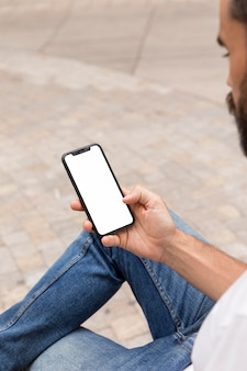 Вид сбоку человека на открытом воздухе, держащего смартфон