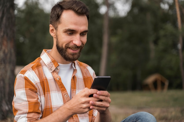 Вид сбоку человека на открытом воздухе, глядя на смартфон