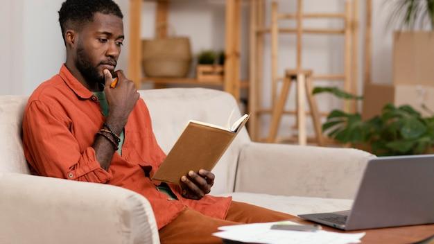 Вид сбоку человека, планирующего косметический ремонт дома с помощью ноутбука и книги