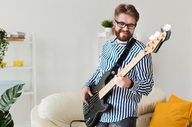 自宅でエレクトリックギターを弾く男の側面図