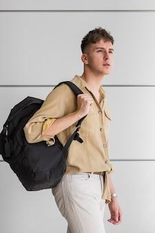 Вид сбоку человека, позирующего на открытом воздухе с рюкзаком