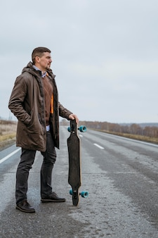 Вид сбоку человека, позирующего со скейтбордом на дороге