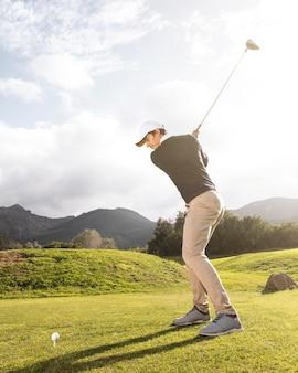 필드에서 골프를 연습하는 사람의 측면보기
